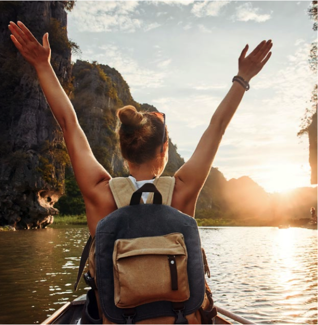 Lady with hands up on a river appearing to be on vacation