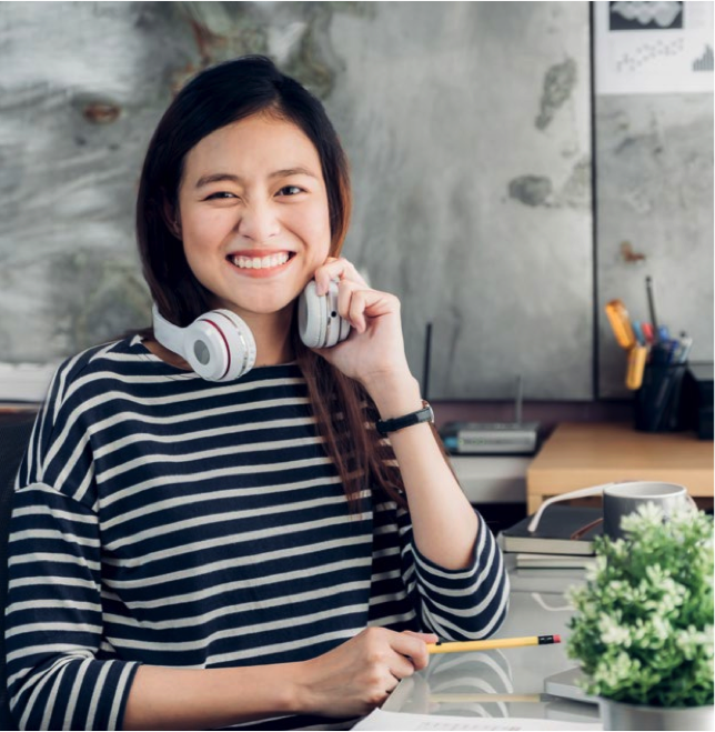 Lady holding head phones smiling because of alternate work schedule